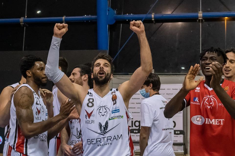 Tavernelli, giocatore del Derthona Basket, festeggia con il pubblico e i compagni di squadra la vittoria in Gara 5 contro Ravenna