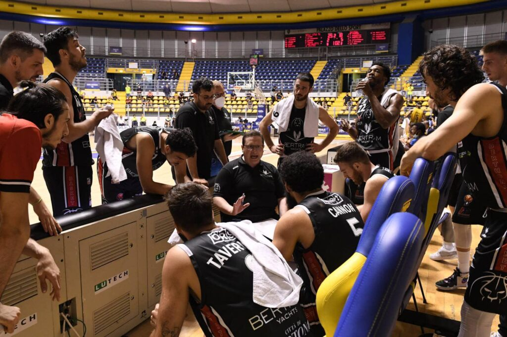 Coach Ramondino a colloquio in panchina con i suoi giocatori durante Gara 1 delle finali playoff tra Derthona Basket e Torino